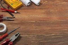 Uppsättning av det elektriska hjälpmedlet på träbakgrund Tillbehör för teknikarbete, energibegrepp royaltyfria foton