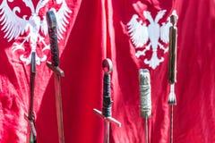 Uppsättning av det medeltida riddaresvärdet och den röda flaggan arkivfoto