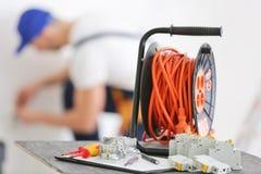 Uppsättning av elektrikerhjälpmedel och den suddiga mannen på arbete Royaltyfri Fotografi