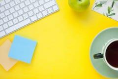 Uppsättning av färgglade klistermärkear, det vita tangentbordet, anteckningsbok och mellanmål arkivfoto