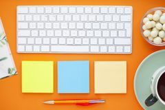 Uppsättning av färgglade klistermärkear, det vita tangentbordet, anteckningsbok och mellanmål arkivbild