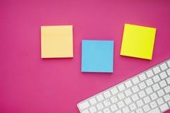 Uppsättning av färgglade klistermärkear, det vita tangentbordet, anteckningsbok och mellanmål fotografering för bildbyråer