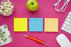 Uppsättning av färgglade klistermärkear, det vita tangentbordet, anteckningsbok och mellanmål royaltyfri fotografi