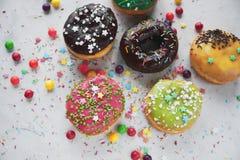 Uppsättning av färgrika hemlagade donuts med isläggning på den vita tabellen Arkivfoton
