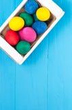 Uppsättning av färgrika påskägg i en vit träask på blåa träbakgrunder Fotografering för Bildbyråer