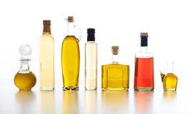 Uppsättning av flaskor av olivolja och vinäger på vit bakgrund Royaltyfri Fotografi