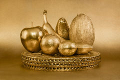 Uppsättning av frukter med den guld- peelen på guld- bakgrund Fotografering för Bildbyråer