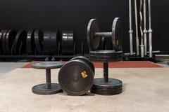 Uppsättning av gamla och använda hantlar för idrottshallsvartmetall Idrottshall- och konditionutrustning arkivfoto
