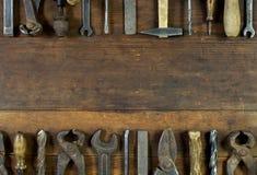 Uppsättning av gamla rostiga hjälpmedel på lantlig träbakgrund arkivbild
