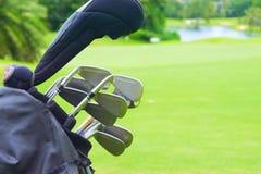 Uppsättning av golfklubbar över grön fältbakgrund Arkivfoto