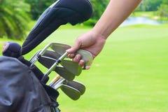 Uppsättning av golfklubbar över grön fältbakgrund Arkivbilder