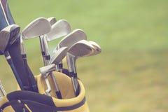 Uppsättning av golfklubbar över grönt fält Royaltyfri Foto