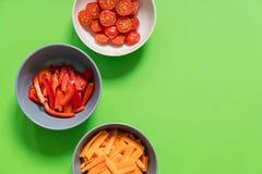 Uppsättning av grönsaker i plattor på röda körsbärsröda tomater för en grön bakgrund, morötter, söta peppar Royaltyfria Foton