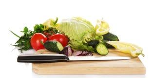 Uppsättning av grönsaker och kniven på skärbrädan Arkivfoton