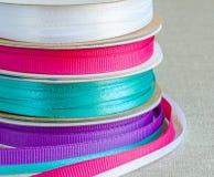 Uppsättning av grosgrainband: blått violet som är karmosinröd, vit Bakgrundssäckväv Fotografering för Bildbyråer