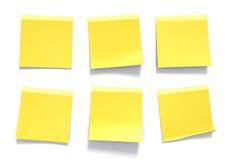 Uppsättning av gula klibbiga anmärkningar som används i ett kontor för påminnelser och viktig information Arkivfoto
