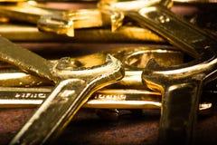 Uppsättning av guld- skiftnycklar på rostig bakgrund Royaltyfri Bild