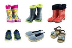 Uppsättning av gummistöveler, gymnastikskor och sandaler för ungar som isoleras på royaltyfri foto