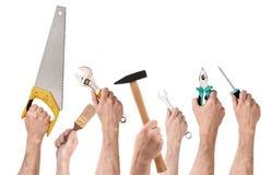 Uppsättning av händer för folk` som s rymmer olika byggnadshjälpmedel isolerade på vit bakgrund Arkivfoto