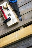 Uppsättning av handhjälpmedel: bågfilen plattång, skruvar, hammare, spikar - på en stång och träunplaned bräden Handhjälpmedel fö Royaltyfri Fotografi