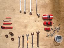 Uppsättning av hjälpmedel för bilen som reparerar på träbakgrund med röda leksakbilar för kontrast Top beskådar fotografering för bildbyråer