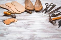 Uppsättning av hjälpmedel för skomakare på vit träbakgrund kopiera avstånd royaltyfri fotografi