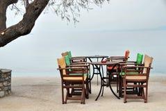 Uppsättning av kafétabell och stolar som väntar på kunder vid havet Royaltyfria Foton