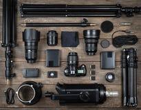 Uppsättning av kameran och fotografiutrustninglinsen, tripod, filter, exponering, minneskort, hårt skrivbord, reflektor på det wo royaltyfri bild