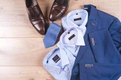 Uppsättning av klassiska mäns kläder - blått dräkt, skjortor, bruntskor, bälte och band på träbakgrund arkivbild