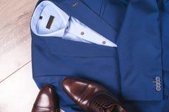 Uppsättning av klassiska mäns kläder - blått dräkt, skjortor, bruntskor, bälte och band på träbakgrund royaltyfria foton