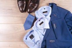 Uppsättning av klassiska mäns kläder - blått dräkt, skjortor, bruntskor, bälte och band på träbakgrund arkivfoton