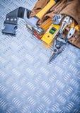 Uppsättning av konstruktion som bearbetar i toolbelt på kanaliserad metallbackg arkivfoto