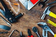 Uppsättning av konstruktionshjälpmedel på träbräde som skiftnyckeln, hammare, pli Arkivbilder