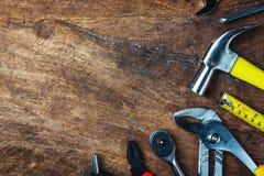 Uppsättning av konstruktionshjälpmedel på träbräde som skiftnyckeln, hammare, pli Royaltyfria Bilder