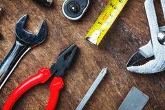 Uppsättning av konstruktionshjälpmedel på träbräde som skiftnyckeln, hammare, pli Fotografering för Bildbyråer