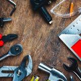 Uppsättning av konstruktionshjälpmedel på träbräde som skiftnyckeln, hammare, pli Royaltyfri Foto
