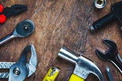 Uppsättning av konstruktionshjälpmedel på träbräde som skiftnyckeln, hammare, pli Arkivbild
