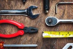 Uppsättning av konstruktionshjälpmedel på träbräde som skiftnyckeln, hammare, pli Royaltyfri Bild