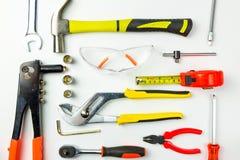 Uppsättning av konstruktionshjälpmedel på vit bakgrund som skiftnyckeln, hammare, Arkivbilder