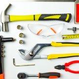 Uppsättning av konstruktionshjälpmedel på vit bakgrund som skiftnyckeln, hammare, Arkivfoto
