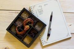 Uppsättning av kryddor i mörkt träfall nära anteckningsboken och pennan som listar ingredienser Royaltyfria Foton