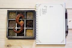 Uppsättning av kryddor i mörkt träfall nära anteckningsboken och pennan som listar ingredienser Royaltyfri Foto
