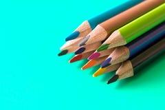 Uppsättning av kulöra blyertspennor i turkosbakgrund Makro Selecti royaltyfria foton
