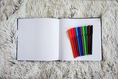 Uppsättning av kulöra pennor och en anteckningsbok på säng Arkivfoton