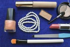 Uppsättning av kvinnors skönhetsmedel och pärlemorfärg halsband på blå bakgrund Royaltyfri Bild