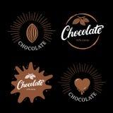 Uppsättning av logoen, etiketten, emblemet eller emblemet för bokstäver för chokladhand den skriftliga med kakaobönan vektor illustrationer