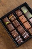Uppsättning av lyxiga handgjorda konfektar i en gåvaask på träbackgroun arkivbild