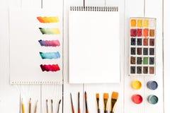 Uppsättning av målarfärger, olika borstar, tom anteckningsbok och färgrika penseldrag på papper Fotografering för Bildbyråer