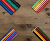 Uppsättning av mångfärgade blyertspennor och markörer på tabellen Royaltyfri Foto