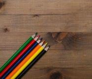 Uppsättning av mångfärgade blyertspennor på trätabellen Arkivbild
